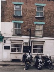 man outside building with motorcycles on street