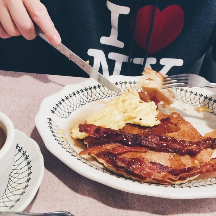 new york city pancakes with eggs and bacon in a diner